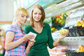 Two women choosing bio food produces fruits supermarket shopping list Royalty Free Stock Image