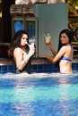 Two women with cocktails in swimming pool Royalty Free Stock Image