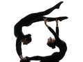 Two women contorsionist exercising gymnastic yoga silhouette practicing in on white background Stock Photo