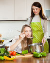 Two women cooking soup together at domestic kitchen focus on blonde Royalty Free Stock Photo