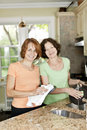 Two women doing dishes in kitchen mother and daughter at home Royalty Free Stock Images