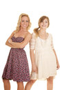 Two women in dresses back to back side smile Royalty Free Stock Photo