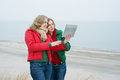 Two women enjoy a digital tablet on the nature standing near sea and looking at Royalty Free Stock Photography