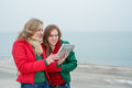 Two women enjoy a digital tablet on the nature standing near sea and looking at Stock Photography