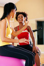 Two women with fitness ball in gym Royalty Free Stock Photo
