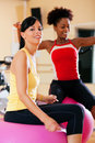 Two women with fitness ball in gym Royalty Free Stock Image