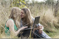 Two women friends sitting outdoors together close with a laptop computer share an intimate moment Royalty Free Stock Images