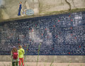 Two women gaze at le mur des je t aime in montmartre paris the wall of i love you france many languages represented on this large Stock Photo