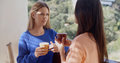 Two women having a friendly chat together at home over refreshments standing enjoying drink overlooking the garden Royalty Free Stock Photos