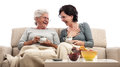 Two women having fun at coffee conversation adult and senior sitting on couch holding cups of or tea and a very funny fruits on Royalty Free Stock Images