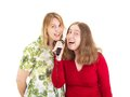 Two women having fun while singing Stock Image