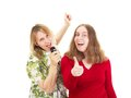 Two women having fun while singing Royalty Free Stock Images