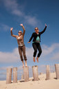 Two women jumping from a row of poles on the beach with lot fun beautiful day Stock Image