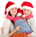 Two women and little girl in Santa hat Stock Image