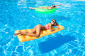 Two women lying on air mattress in the swimming pool Royalty Free Stock Photo