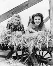 Two women lying in a wagon of hay with their legs in the air Royalty Free Stock Photo