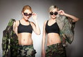 Two women in military clothes army girls and sunglasses on gray background Royalty Free Stock Photo