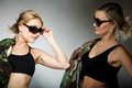 Two women in military clothes army girls and sunglasses on gray background Stock Image