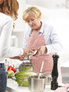 Two women mother and daughter cooking together in the kitchen Stock Images