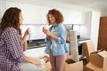 Two women moving into new home and unpacking boxes having a cup of coffee Stock Photography