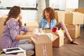 Two women moving into new home and unpacking boxes in kitchen laughing Stock Photography