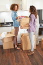 Two women moving into new home and unpacking boxes in kitchen smiling at each other Royalty Free Stock Images