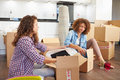 Two women moving into new home and unpacking boxes sitting on kitchen floor Stock Photos