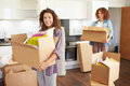 Two women moving into new home and unpacking boxes whilst looking to camera smiling Royalty Free Stock Image