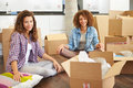Two women moving into new home and unpacking boxes whilst sitting on floor smiling to camera Stock Image