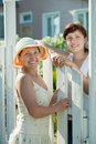 Two  women near fence wicket Stock Photo