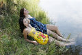 Two women outdoors river dresses feet in water reclining on bank Stock Photos