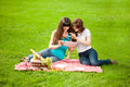 Two women in the park on a picnic with a Tablet PC Royalty Free Stock Photo