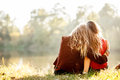 Two women rear view young sitting on grass hugging Royalty Free Stock Images