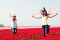 Two women in a red tulip field young jumping outdoors Royalty Free Stock Photo