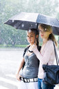 Two women in a riany weather Stock Images
