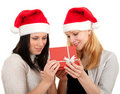 Two women in Santa hat keeping red box Stock Images