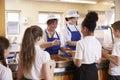 Two Women Serving Kids Food In...