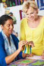 Two women sewing quilt together and talking Royalty Free Stock Photography