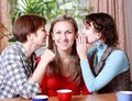 Two women share secrets with a friend Royalty Free Stock Photography