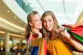 Two women shopping with bags in mall female friends having fun while a Royalty Free Stock Photography