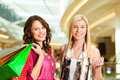 Two women shopping with bags in mall female friends having fun while a Royalty Free Stock Image