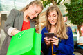 Two women shopping with bags in mall female friends having fun while a they bought a e book Stock Images