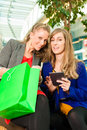Two women shopping with bags in mall female friends having fun while a they bought a e book Stock Photography