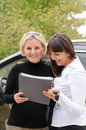 Two women signing a contract to buy a car standing in front of the vehicle with the paperwork and keys smiling happily Stock Photo