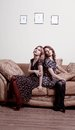 Two women sitting back to back Stock Photos
