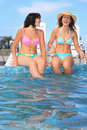 Two women sitting on ledge pool open-air Stock Image