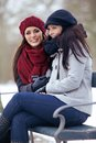 Two women sitting outdoors on a cold winter happy park bench Royalty Free Stock Photo