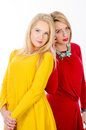 Two women standing in yellow and red dresses studio portrait of a young back to back wearing white background Stock Photography