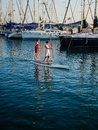 stock image of  Two women surfing on sups in Tel Aviv port in front of harbored boats and yachts