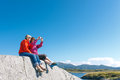 Two women taking photo of norwegian landscape sitting on stone with fjord kvernesfjorden Royalty Free Stock Image
